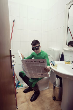 Superhero reading a financial newspaper on a toilet and relaxing. photo