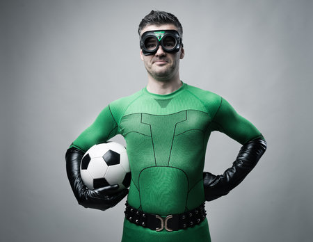 funny guys: Confident superhero in green costume holding a soccer ball.