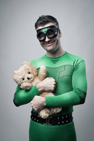 Smiling cheerful superhero holding a cute teddy bear. Banque d'images