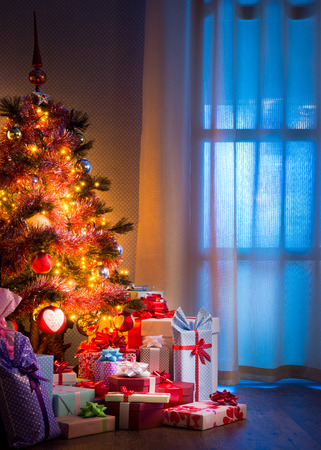 Christmas eves night with colorful gifts and tree with lights. photo