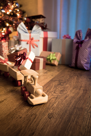 christmas celebration: Wooden toy train with special gift and christmas tree on background.