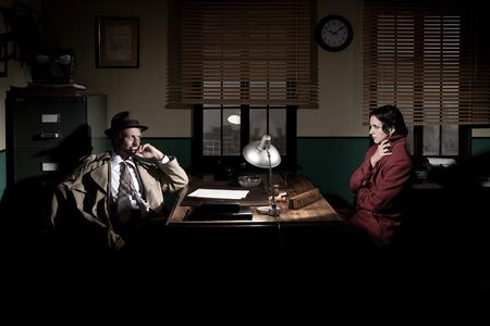 사무실 책상에서 잘 생긴 형사 인터뷰 젊은 여성, 1950 년대 필름 누아르 스타일.