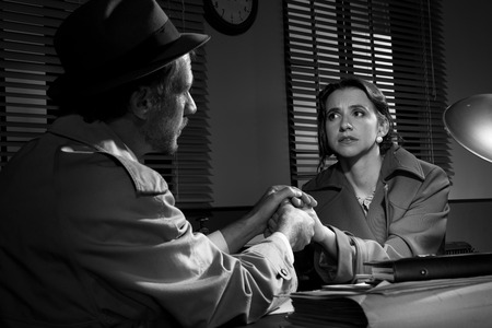 Handsome supportive detective at office desk holding a young womans hands and comforting her, film noir. photo