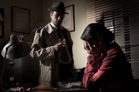 Desperate woman crying head in hands and confident detective standing in his office. photo