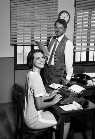 dictating: Directora con el papeleo y la secretaria joven a escribir en m�quina de escribir en una oficina elegante de la vendimia. Foto de archivo