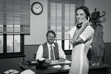 answering phone: Secretario de 1950 a llamadas telef�nicas j�venes en la oficina del director y sonriendo. Foto de archivo