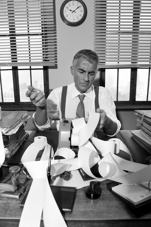 Confused pensive accountant checking very long bills on cash register tape, 1950s style office. photo