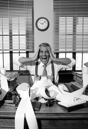 Desperate accountant shouting head in hands in vintage 1950s style office. photo