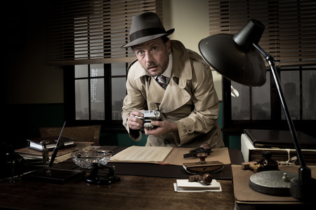 secret: Retro spy agent caught photographing important documents on office desk, 1950s style.