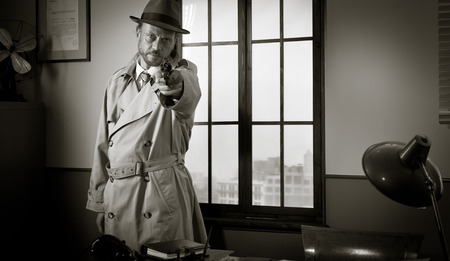 violence in the workplace: Man in trench coat and hat pointing a revolver with vintage office on background, film noir.