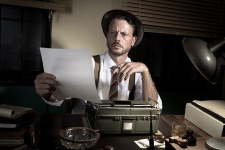 reportero: Reportero 1950 trabajando hasta tarde en la noche y la corrección de pruebas de su trabajo.