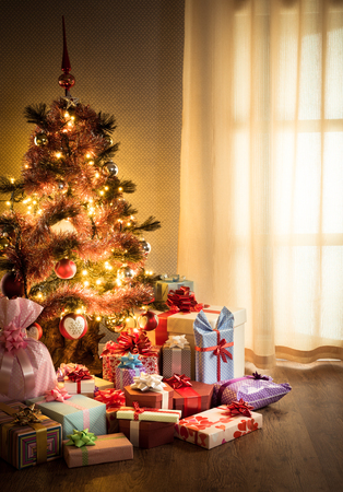 christmas tree decorations: Colorful gifts in front of an elegant christmas tree in the living room.