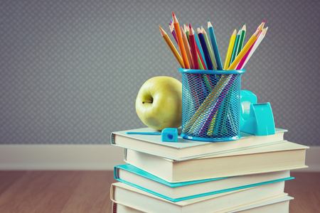 pencil holder: Color wooden pencils with apple and stack of books, back to school concept.