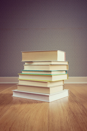 stacked books: Stack of hardcover books on parquet floor with dotted wallpaper on background.