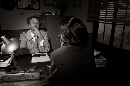 Handsome detective at office desk interviewing a young woman, 1950s film noir style. photo