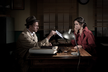witness: Handsome detective at office desk showing a picture to a young woman, film noir scene.