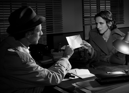 Woman handing over an envelope to a detective at police station, 1950s film noir style. Stock Photo