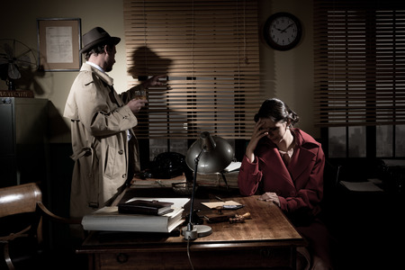 Confident detective standing in his office interviewing a young sad woman. photo
