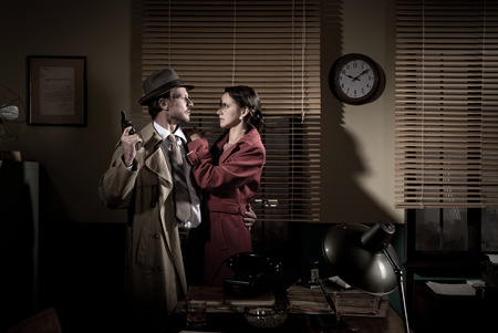 Passionate vintage couple embracing in detectives office holding a gun.