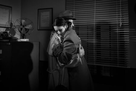woeful: Detective consoling and hugging a young woman in his office, film noir scene.