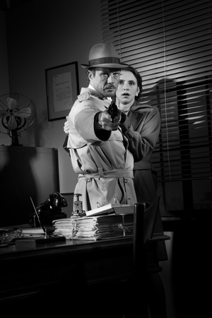 thriller: Brave detective pointing a gun and young scared woman hiding behind him, 1950s film noir style. Stock Photo
