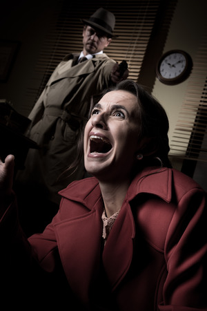 woman screaming: Detective standing in the dark and pointing a gun to a screaming woman.