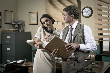 Young secretary on the phone and director working together, 1950s vintage style office. photo