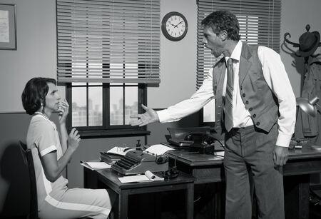 personas discutiendo: Director Furious discutiendo con joven secretaria, oficina 1950 de la vendimia. Foto de archivo