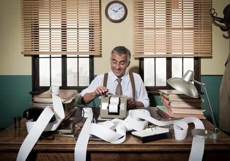 Busy vintage accountant with adding machine surrounded by cash register tape. Foto de archivo