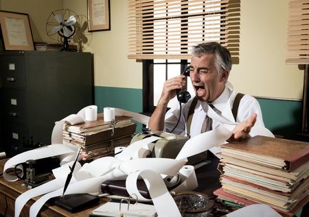 マシンのテープを追加することによって囲まれた電話で大声で叫んで怒っているヴィンテージのビジネスマン。