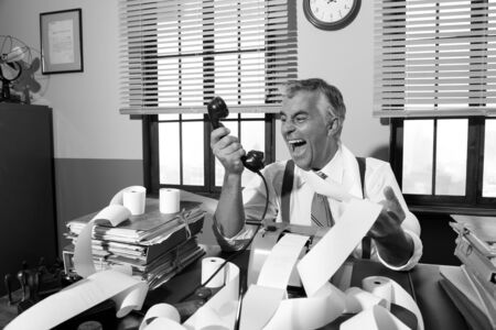 over burdened: Angry vintage businessman shouting out loud at phone surrounded by adding machine tape.