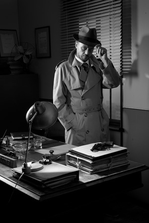 office force: Attractive detective standing next to his desk, 1950s style office.