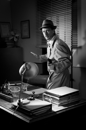pointing gun: Attractive detective pointing a gun next to a desk, 1950s style office.