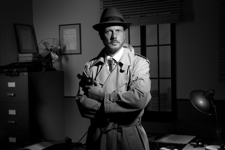 Attractive detective holding a revolver with retro office on background, film noir.