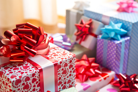birthday presents: Elegant colorful gift boxes with huge ribbon close-up on the floor. Stock Photo