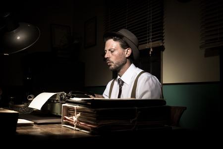 Vintage reporter working late at night typing on typewriter. Stok Fotoğraf