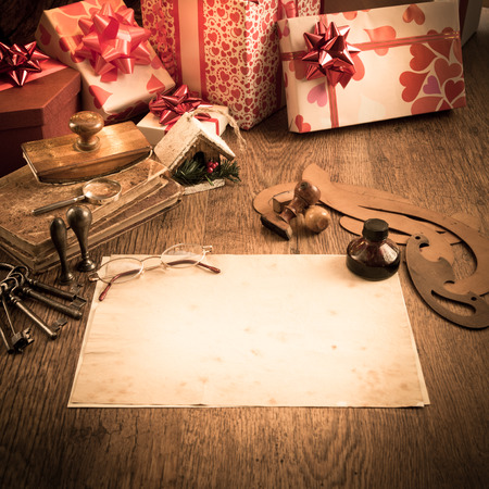 wishlist: Old letter with feather pen and glasses, gifts and christmas tree on background.