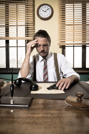 businessman waiting call: Depressed businessman sitting at desk and holding a gun, 1950s style office.