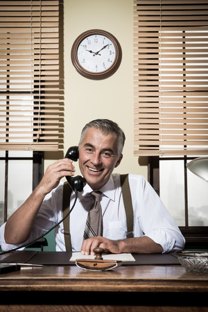 desk tidy: Smiling handsome businessman on the phone working at desk, 1950s vintage office. Stock Photo
