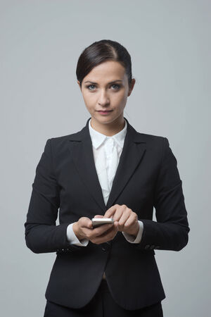 business woman phone: Smiling confident business woman using touch screen mobile phone.