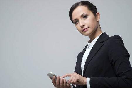 touch screen phone: Smiling confident business woman using touch screen mobile phone.