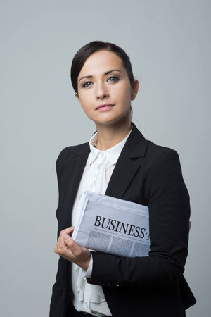 financial newspaper: Attractive confident businesswoman with black jacket holding financial newspaper.