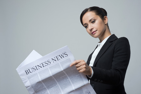 finance director: Attractive confident businesswoman with black jacket holding financial newspaper.