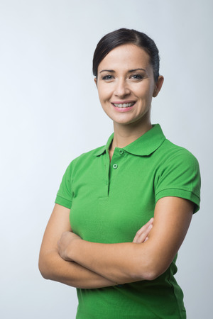 Smiling cheerful young woman in green polo t-shirt with arms crossed.