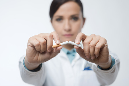 stop smoking: Stop smoking concept with female doctor breaking a cigarette.