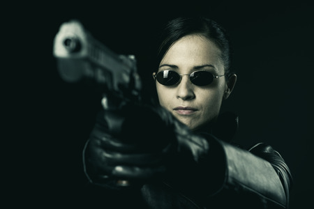 Attractive female criminal in black leather coat pointing a gun.