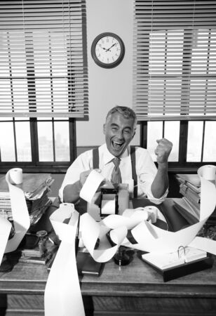 cash desk: Cheerful accountant Surrounded by vintage adding machine paper tape in His office.