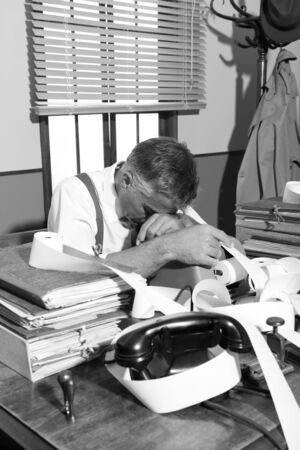 over burdened: Tired overworked accountant sleeping on his messy desk, 1950s style office.