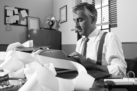 Professional accountant working with adding machine tape in vintage office. photo