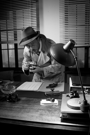 gun room: Back spy agents caught photographing important documents on office desk, 1950s style.